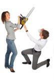 Protegen al hombre joven contra muchacha con la motosierra foto de archivo