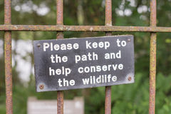 Protegga il contrassegno della fauna selvatica sul portone che conduce alla via della foresta fotografia stock libera da diritti