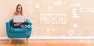 Protegido con la mujer joven que usa el ordenador portátil imagen de archivo libre de regalías