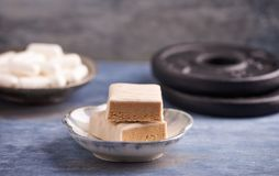 Protein chocolate bar in two pieces and plates. Nutrition for bodybuilding. Fitness supplements on rustic wooden backgroun royalty free stock images