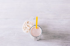 Protein cocktail with a straw in a glass and scoop on a white wo Stock Images