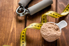 Protein powder for fitness nutrition to start training and measure tape wooden background Stock Image