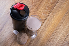 Protein shake, shaker and round scoop. Chocolate protein shake, shaker and round scoop stock photos