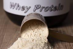 Proteina del siero Mestolo caduto con sapore della polvere della vaniglia Di legno fotografie stock
