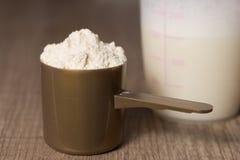 Proteina del siero Mestolo dorato con la polvere di sapore della vaniglia, agitatore immagine stock libera da diritti