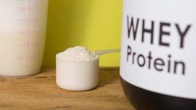 Proteina del siero Vista frontale del mestolo con la polvere, il barattolo e la s della vaniglia Fotografia Stock
