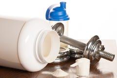 Proteina proszek w scoope z dumbbells w tle - serwatka fotografia stock