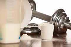 Proteina proszek w scoope z dumbbells w tle - serwatka zdjęcie stock