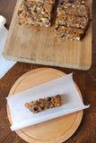 Proteinmüsliriegel mit Nüssen und Trockenfrüchten auf BackenPergamentpapier bei der Verpackung Stockfotos