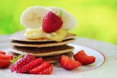 Proteinowi bliny z miodem, bananem i truskawkami, zdjęcia royalty free