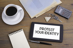 Proteja su identidad Mande un SMS en el dispositivo de la tableta en una tabla de madera Fotos de archivo
