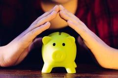 Proteja sus ahorros - con las manos cubriendo la hucha Imagen de archivo libre de regalías