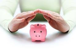 Proteja sus ahorros - con las manos y la hucha imagenes de archivo