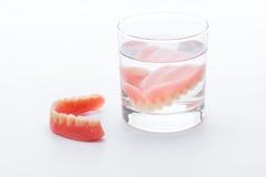Protesi dentaria piena in bicchiere d'acqua su fondo bianco Fotografia Stock Libera da Diritti