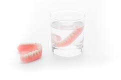 Protesi dentaria piena in bicchiere d'acqua su fondo bianco Fotografia Stock