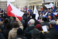The crowd of people holding polish and european union national flag in the city center Royalty Free Stock Photo