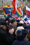 The crowd of elderly people clapping and holding national flag and flag LGBT in the city center Royalty Free Stock Photos