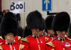 Protest at Baroness Thatcher's funeral. A protester displays a placard disapproving of Baroness Thatcher, behind the band of the British Army Guard's Regiment royalty free stock photography