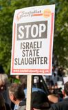 Protest messages on placards and posters at the Gaza: Stop The Massacre rally in Whitehall, London, UK. Hundreds of protesters with placards gathered for the Royalty Free Stock Photos
