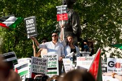 Protest messages on placards and posters at the Gaza: Stop The Massacre rally in Whitehall, London, UK. Hundreds of protesters with placards gathered for the Stock Photography