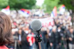 Political protest. Demonstration. Microphone in focus against bl. Protest. Public demonstration. Microphone in focus against blurred audience royalty free stock photo