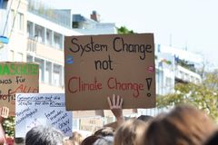 Protest sign saying `System change not climate change` held up by young people during Global Climate Strike