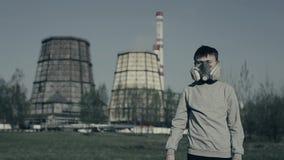 Protesta contra la contaminación atmosférica El individuo joven muestra el finger abajo contra las chimeneas de la fábrica Las de metrajes