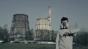 Protesta contra la contaminación atmosférica El individuo joven muestra el finger abajo contra las chimeneas de la fábrica Las de almacen de metraje de vídeo