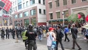 Protestadores e linha de polícia que anda para se filme
