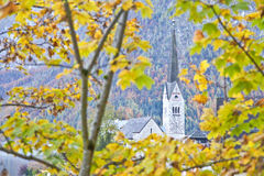 Protestant church through yellow leaves in Hallstatt Royalty Free Stock Image