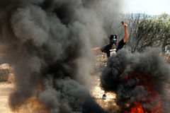 Protestataire palestinien avec la fronde parmi la fumée Photographie stock