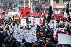 Protestataires tenant tout le genre de signes, de drapeaux et de plaquettes dans les rues Photos stock