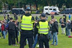 Protestateurs de observation de police photographie stock libre de droits