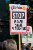 Protesteerder met aanplakbiljet in Gaza: Houd de Slachtingsverzameling in Whitehall, Londen, het UK tegen stock fotografie