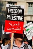 Protesteerder met aanplakbiljet in Gaza: Houd de Slachtingsverzameling in Whitehall, Londen, het UK tegen royalty-vrije stock fotografie