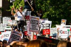 Protesteerders met aanplakbiljetten in Gaza: Houd de Slachtingsverzameling in Whitehall, Londen, het UK tegen stock afbeeldingen