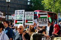 Protesteerders met aanplakbiljetten in Gaza: Houd de Slachtingsverzameling in Whitehall, Londen, het UK tegen stock afbeelding
