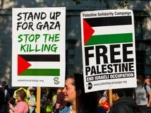 Protesteerders met aanplakbiljetten in Gaza: Houd de Slachtingsverzameling in Whitehall, Londen, het UK tegen royalty-vrije stock foto's