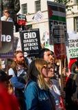 Protesteerders met aanplakbiljetten in Gaza: Houd de Slachtingsverzameling in Whitehall, Londen, het UK tegen royalty-vrije stock fotografie