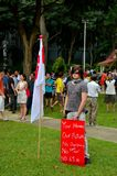 Protester with flag and placard: Singapore rally Royalty Free Stock Image