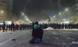 Protester knees during protests against government in Bucharest Royalty Free Stock Image