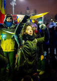 Protester lighting yellow colour, Romania. BUCHAREST, ROMANIA - FEBRUARY 2017: The13th day of protests in Bucharest. Girl with yellow light forming national flag royalty free stock photo