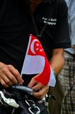 Protester plants flag on bicycle at Singapore rally Royalty Free Stock Photography