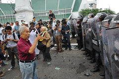 Protester and Police. An unidentified protester from the nationalist Pitak Siam group shouts abuse at a police line during a large anti-government rally on Royalty Free Stock Photos