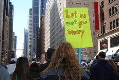 Weary, Tired, March for Our Lives, Protest, NYC, NY, USA. A protester on 6th Avenue carries a sign saying,`Let Us Not Grow Weary,` during the March for Our Lives Royalty Free Stock Images