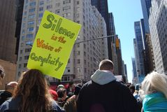 Complicity, Silence, March for Our Lives, Protest, NYC, NY, USA. A protester on 6th Avenue carries a sign saying, `Silence is the voice of complicity,` during royalty free stock photography