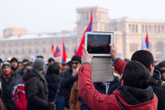 A protester uses a tablet to photograph protest. YEREVAN, ARMENIA – JANUARY 18: Activists and opposition protesting against a controversial new obligatory Royalty Free Stock Image