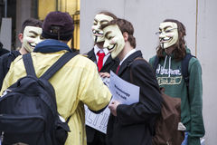 .A protester wearing a Guy Fawkes mask holds a placard  Stock Photos