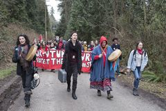 Protesters approach Kinder Morgan tank farm in Burnaby, BC. Protesters carrying banners walk towards the Burnaby tank farm in BC on March 20th, 2018 to protest royalty free stock photo