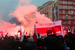 Independence Day March in Warsaw Poland Marred by Violence and Controversy. Protesters and a banner are seen from behind, smoke from flares can be seen at the Stock Image